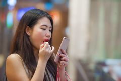Beautiful and happy Asian Chinese woman retouching lips with lipstick makeup looking at mobile phone using it as mirror carrying s. Lifestyle indoors portrait of stock photography