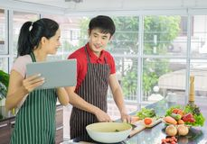 Beautiful happy asian couple are cooking in the kitchen. prepare salad food for diner. Man and Woman smiling looking menu from tab stock photo