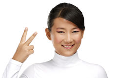 Beautiful happy asian girl showing victory positive sign Royalty Free Stock Photos
