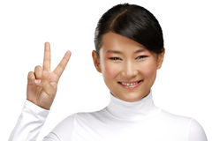 Beautiful happy asian girl showing victory positive sign Royalty Free Stock Photography