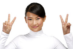 Beautiful happy asian girl showing victory positive sign. On white Stock Photography