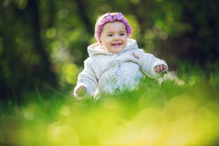 Beautiful happy baby girl sitting on green grass Stock Photo