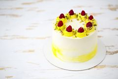 Beautiful happy birthday cake with mascarpone decorated with raspberry, pistachio and candles. Beautiful happy birthday cake with mascarpone decorated with stock photo