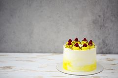Beautiful happy birthday cake with mascarpone decorated with raspberry, pistachio. On the cake stand stock photo