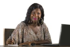 Happy black afro American business woman working cheerful with laptop computer by business district window desk in corporate royalty free stock photo