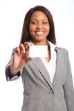 Beautiful happy black woman with business card. Smiling young beautiful business woman wearing grey suit, holding up a business card. Focus point has been pulled Royalty Free Stock Photo