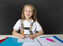 Beautiful happy blond junior schoolgirl smiling while doing school homework writing on notepad with pen Stock Photo