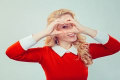 Woman looking at camera through heart gesture royalty free stock image