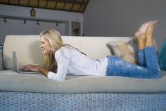Beautiful and happy blond woman early 40s relaxed at home living room using internet on laptop working lying comfortable on sofa a royalty free stock image