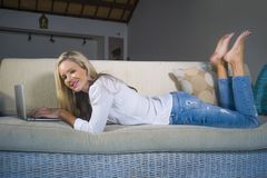 Beautiful and happy blond woman early 40s relaxed at home living room using internet on laptop working lying comfortable on sofa a stock image