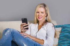 Beautiful happy blond woman early 40s relaxed at home living room using internet social media on mobile phone smiling sitting comf. Beautiful and happy blond Stock Image