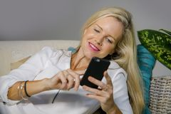 Beautiful happy blond woman early 40s relaxed at home living room using internet social media on mobile phone smiling lying comfor. Beautiful and happy blond Royalty Free Stock Photography