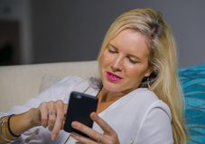 Beautiful happy blond woman early 40s relaxed at home living room using internet social media on mobile phone smiling lying comfor. Beautiful and happy blond Stock Photos