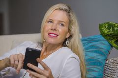 Beautiful happy blond woman early 40s relaxed at home living room using internet social media on mobile phone smiling lying comfor. Beautiful and happy blond Stock Photography