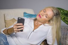 Beautiful happy blond woman early 40s relaxed at home living room using internet social media on mobile phone smiling lying comfor. Beautiful and happy blond Royalty Free Stock Photos