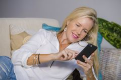Beautiful happy blond woman early 40s relaxed at home living room using internet social media on mobile phone smiling lying comfor. Beautiful and happy blond Royalty Free Stock Image