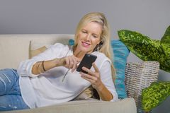 Beautiful happy blond woman early 40s relaxed at home living room using internet social media on mobile phone smiling lying comfor. Beautiful and happy blond Stock Photo