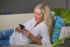 Beautiful happy blond woman early 40s relaxed at home living room using internet social media on mobile phone smiling lying comfor. Beautiful and happy blond Royalty Free Stock Images