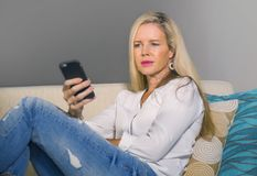 Beautiful happy blond woman early 40s relaxed at home living room using internet social media on mobile phone smiling sitting comf. Beautiful and happy blond Stock Photos