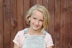 Beautiful and happy blonde girl smiles. Portrait on the background of a wooden wall. Royalty Free Stock Photography