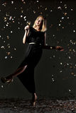 Beautiful happy blonde woman holding glass of white wine on black background with confetti Stock Photo