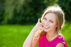 Beautiful happy blonde woman making a call me gesture Stock Image