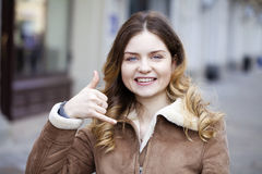 Beautiful happy blonde woman making a call me gesture Royalty Free Stock Image