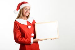 Smiling blonde woman in Santa Claus clothes with white board. Beautiful happy blonde woman in Santa Claus clothes smiling with white board in her hands. Young Royalty Free Stock Photos