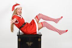 Funny blonde woman in Santa Claus clothes on white background. Beautiful happy blonde woman in Santa Claus clothes and striped socks moving her legs. Young funny Stock Photography