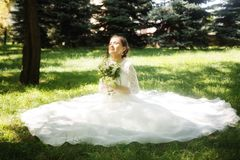 Beautiful happy bride with bouqet. In the park stock photography