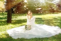 Beautiful happy bride with bouqet. In the park stock photo