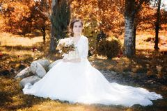 Beautiful happy bride with bouqet. In the park royalty free stock image
