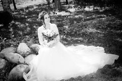 Beautiful happy bride with bouqet. In the park royalty free stock photo