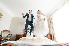 Beautiful happy bride and groom jumping on the bed in rich hotel interior Royalty Free Stock Photos