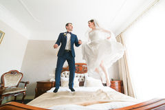 Beautiful happy bride and groom jumping on the bed in rich hotel interior Stock Photo