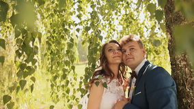 Beautiful and happy bride and groom under the branches of the birch trees rejoice together. Cheek to cheek with closed stock footage