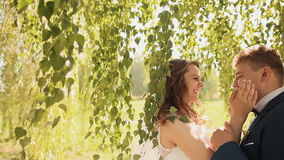 Beautiful and happy bride and groom under the branches of the birch trees rejoice together. Touching hands. Beautiful and happy bride and groom under the stock video