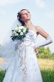 Beautiful happy bride looks down Stock Photography