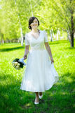 Beautiful happy bride walking on the green grass Royalty Free Stock Images