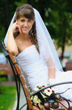Beautiful happy bride in a white dress sitting on bench Stock Images