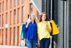 Beautiful happy brunette and blond walking holding hands Royalty Free Stock Photo