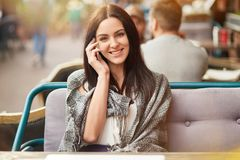 Beautiful happy brunette female with gentle smile, speaks via smart phone with friend, shares latest news, poses in outdoor cafe,. Looks positively at camera Stock Photo
