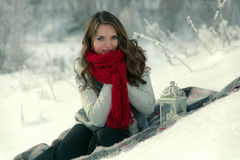 Beautiful happy brunette girl in a red knitted scarf sitting on a blanket on the snow in winter on background of trees Royalty Free Stock Image