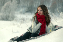 Beautiful happy brunette girl in a red knitted scarf sitting on a blanket on the snow in winter on background of trees Royalty Free Stock Photography