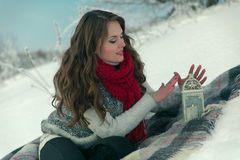 Beautiful happy brunette girl in a red knitted scarf sitting on a blanket on the snow in winter on background of trees Royalty Free Stock Photos