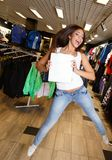 Beautiful happy brunette girl with shopping bag. Jumping in a sport outlet Stock Photos