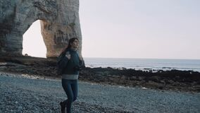 Beautiful happy brunette tourist woman with camera and backpack exploring white arch sea rocks near Etretat slow motion. stock footage