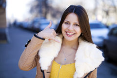 Beautiful happy brunette woman making a call me gesture Stock Images