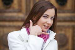 Beautiful happy brunette woman making a call me gesture Stock Photo