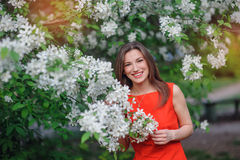 Beautiful happy brunette woman in the park on a warm summer day Stock Photos